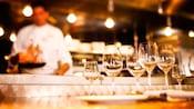 Plusieurs verres de vin sur un bar, avec une cuisine ouverte en arrière-plan