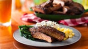 Barbecue ribs, mashed potatoes, corn and green beans on a plate near a dish of barbecue ribs