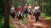 Cinco hóspedes e uma funcionária andando a cavalo ao longo de uma trilha no bosque
