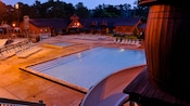 A pool lit up after dark at The Campsites at Disney's Fort Wilderness Resort
