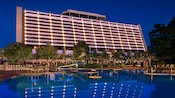 A poolside view of the rear of Disney's Contemporary Resort, lit up at night