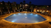 High, wide view of the Casitas quiet pool surrounded by palm trees, lit up at night