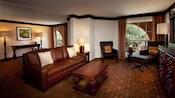 Un gabinete con TV, 2 butacas, una mesa ratona y un sofá cama Queen Size junto a un área de ingreso y puerta principal