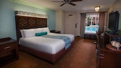 Una cama King Size frente a una cómoda con TV, escritorio y, detrás, una ventana con vista a la piscina y una puerta del frente