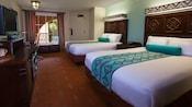 Duas camas queen em frente a uma cômoda com TV e escrivaninha, e, atrás, uma janela e uma porta da frente