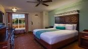 Uma cama king em frente a uma cômoda com TV, escrivaninha e, atrás, 2 pufes perto de uma janela e uma porta da frente