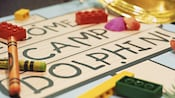 Close up of a Welcome to Camp Dolphin! sign with 2 crayons and 3 toy building bricks on it