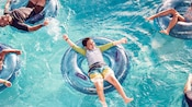 Several people in a swimming pool, floating on personal inner tubes