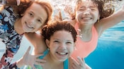 Three young girls smiling underwater in a swimming pool