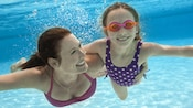 Mother and daughter swim together underwater in a pristine pool