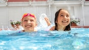 Two little girls playing in the pool.