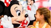 Minnie Mouse high fives a happy little girl during a Character Greeting event at the parks