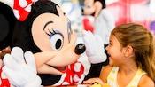 Minnie Mouse fait un «tope là» à une petite fille heureuse lors d'une rencontre avec les personnages dans les parcs