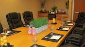 Sala de conferencias con sillas, una mesa preparada y una barra, con un minirrefrigerador, té, jugo y frutas