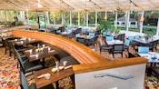 Un restaurant avec des tables mises, des chaises et une vue sur des palmiers avec un belvédère