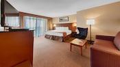 Una habitación con una cama, un TV, una mesa ratona, una silla, un sofá, una lámpara y un cuadro