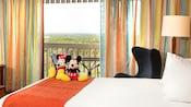 Una habitación con vista, una cama con peluches de Mickey y Minnie, un balcón de patio externo con una mesa y sillas, otra silla y una lámpara