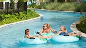 2 kids and a woman float in a tract of water on inner tubes with words that read Float Lagoon