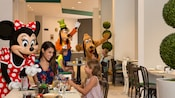 Goofy, Minnie Mouse and Pluto interact with children in a restaurant