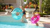 2 niñas con flotadores se zambullen en una piscina