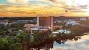Une vue d'un hôtel avec des arbres, un lac, une piscine et une montgolfière