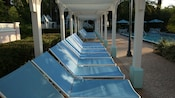 Row of blue lounge chairs under a long white portico near Magnolia Bend quiet pool