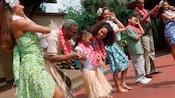 Uma garotinha usando colar e saia havaianos sorrindo enquanto dançarinos de hula ensinam sua família a dança hula