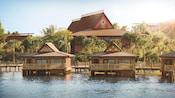 Trois bungalows sur pilotis reflètent l'ambiance du Pacifique Sud, ils sont dotés de décorations en bois et entourés de palmiers.