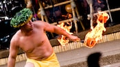 A shirtless Cast Member in Polynesian outfit twirling a flaming baton