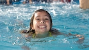 A young female Guest smiling while she enjoys a swim in a pool at Disney's Port Orleans Resort