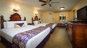 Deux grands lits avec des têtes de lits en bois et une table de chevet, face à une commode, téléviseur, 2chaises et miroir