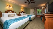 2 colonial-style beds and headboards, wall sconces, dresser and TV, ceiling fan, curtained window