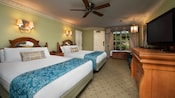 2 beds with headboards in colonial-themed room with dresser, TV, curtained window with river view