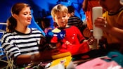 Un membre de l'équipe aide un petit garçon avec son projet de bricolage