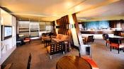 Un coin salon dans un hôtel de Walt Disney World Resort à côté d'une salle avec une table de buffet offrant des produits de boulangerie-pâtisserie