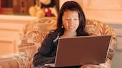 Un client assis dans un fauteuil entièrement rembourré utilise un ordinateur portable pour faire une recherche sur Internet
