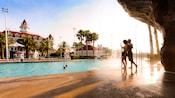 Un homme et une femme profitant de la cascade de la Beach Pool du Disney'sGrandFloridianResort&Spa.
