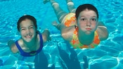 Two girls in bathing suits swim underwater in a pool