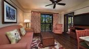 Sofá y almohadas, mesa ratona, obra de arte en la pared, TV de pantalla plana, balcón con cortinas con vista a pinos, sillón