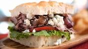 Un sándwich relleno con cebollas caramelizadas, carne de ternera, queso azul, rodajas de tomate y lechuga