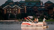 A boat on the water with 3 men fishing in front of Wilderness Lodge Resort