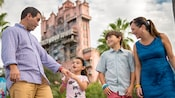 A young girl takes her father's hand in excitement as her older and brother look on in front of the Twilight Zone Tower of Terror
