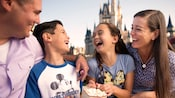 A brother and sister share a laugh and a box of popcorn with their parents in front of Cinderella Castle