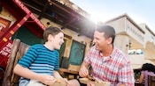 A father and son enjoy grilled chicken skewers outside Harambe Market