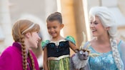 A little girl wearing a princess costume and carrying a plush Sven toy stands in between Princess Anna and Queen Elsa