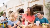 Une mère et sa fille sourient en savourant un repas à une table extérieure