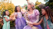 Three young girls gather around Rapunzel outside of Princess Fairytale Hall