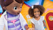 A smiling little girl meets Doc McStuffins