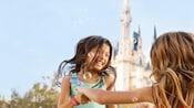 A smiling young girl playfully dances with another young girl in front of Cinderella Castle as bubbles float around them