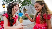 Princess Elena of Avalor shows her jeweled scepter to a smiling little girl wearing an Elena costume